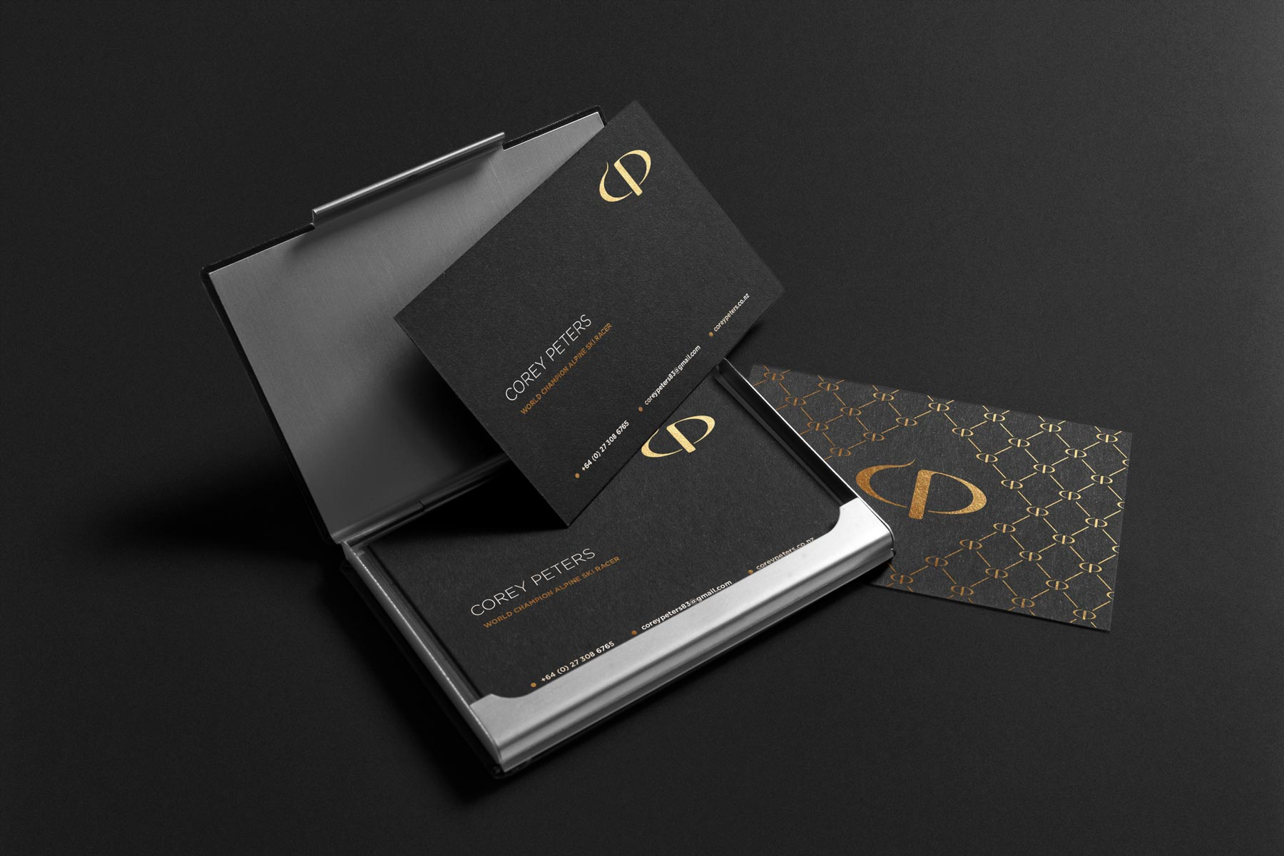 Corey Peters business cards black with gold logo and brand identity displaying front and back examples
